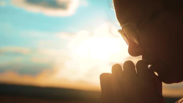 girl praying. girl folded her hands in prayer silhouette sunset. slow motion video. Girl folded her hands in prayer pray to God. asks forgiveness for sins of repentance. believing girl. lifestyle