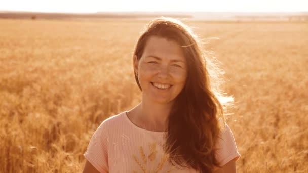 portré gyönyörű nő mosolyogva. lány divat modell lassú mozgás video fehér ruha, a mező a búza. szexi nő a természet, fű mező virág nyáron. a mezőgazdaság. életmód lány hossza