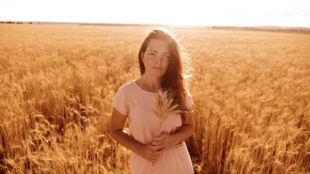 portrét krásná žena s úsměvem. Modelka dívka v zpomalené video bílých šatech na pole pšenice. sexy žena na přírodu v létě květiny trávy životní styl pole. zemědělství. Délka dívka