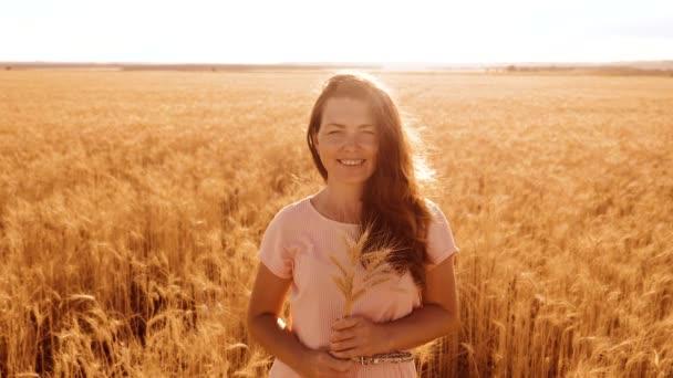 portrét krásná žena s úsměvem. Modelka dívka v zpomalené video bílých šatech na pole pšenice. sexy žena na přírodu v létě životní styl pole trávy květiny. zemědělství. Délka dívka