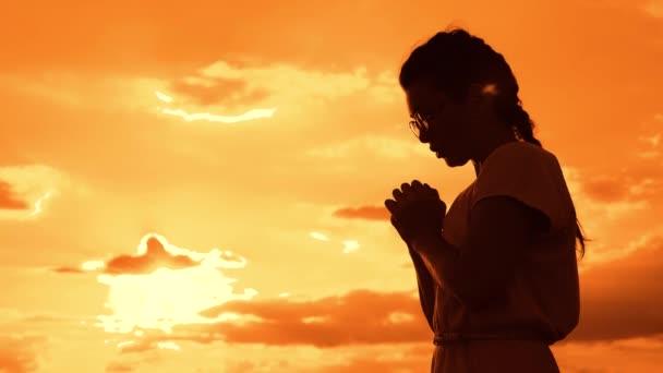 betet das Mädchen. Mädchen faltete ihre Hände im Gebet Silhouette bei Sonnenuntergang. Zeitlupenvideo. Mädchen faltete ihre Hände im Gebet und betete zu Gott. Mädchen betet bittet um Vergebung für Sünden Lebensstil der Reue