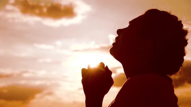 betet das Mädchen. Mädchen faltete ihre Hände im Gebet Silhouette bei Sonnenuntergang. Zeitlupenvideo. Mädchen faltete ihre Hände im Gebet und betete zu Gott. Mädchen, das betet, bittet um Vergebung für Sünden der Reue