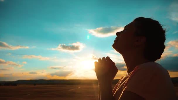 Mädchen betet. Mädchen faltete ihre Hände im Gebet Silhouette bei Sonnenuntergang. Zeitlupenvideo. Mädchen faltete ihre Hände im Gebet und betete zu Gott. bittet um Vergebung für die Sünden der Reue. gläubige Mädchen