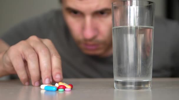 man taking pills at home is ill sick slow motion video. Healthcare and medical concept disease. lifestyle male takes a pill and drinks a glass of water indoors