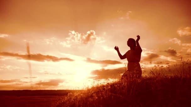 Mädchen faltete ihre Hände im Gebet Lifestyle Silhouette bei Sonnenuntergang. Frau, die auf Knien betet. Zeitlupenvideo. Mädchen faltete ihre Hände im Gebet und betete zu Gott. das betende Mädchen bittet um Vergebung für die Sünden