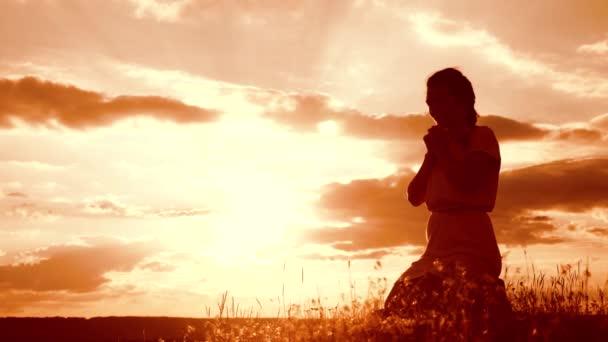 Dívka složila si ruce v modlitbě silueta při západu slunce. Žena se modlí na kolenou. zpomalené video. koncept křesťanství náboženství katolicismus. Dívka složila si ruce v modlitbě modlit se k Bohu. dívka