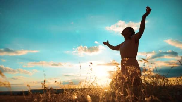 Žena se modlí na kolenou. Dívka složila si ruce v modlitbě silueta při západu slunce. zpomalené video. Dívka složila si ruce v modlitbě životního stylu modlit se k Bohu. dívka se modlí požádá o odpuštění za hříchy