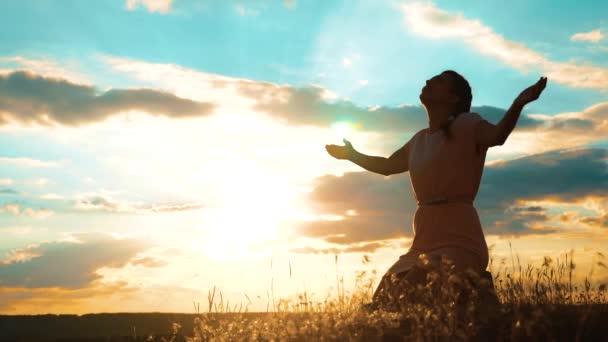 Mädchen faltete ihre Hände zum Gebet bei Sonnenuntergang. Frau, die auf Knien betet. Zeitlupenvideo. Mädchen faltete ihre Hände im Gebet und betete zu Gott. das betende Mädchen bittet um Vergebung für die Sünden