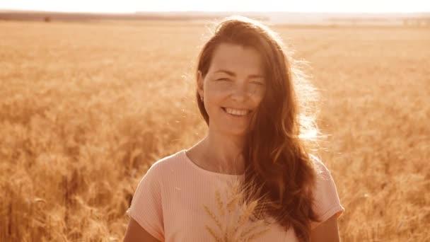 portrét krásná žena s úsměvem. Modelka dívka v zpomalené video bílých šatech na pole pšenice. sexy žena na přírodu v létě květy pole trávy. zemědělství. Délka životního stylu holka
