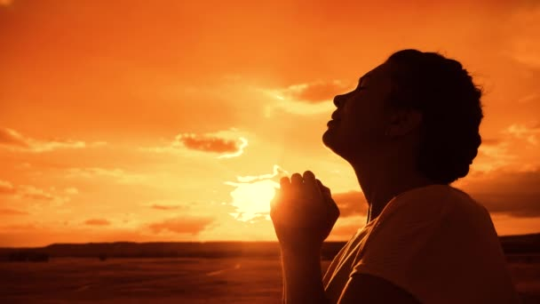 betet das Mädchen. Mädchen faltete ihre Hände im Gebet Silhouette bei Sonnenuntergang. Slow-Lifestyle-Video. Mädchen faltete ihre Hände im Gebet und betete zu Gott. Mädchen, das betet, bittet um Vergebung für Sünden der Reue