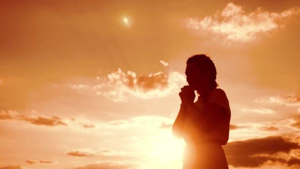 Frau, die auf Knien betet. Mädchen faltete ihre Hände im Gebet Lifestyle Silhouette bei Sonnenuntergang. Zeitlupenvideo. Mädchen faltete ihre Hände im Gebet und betete zu Gott. das betende Mädchen bittet um Vergebung für die Sünden