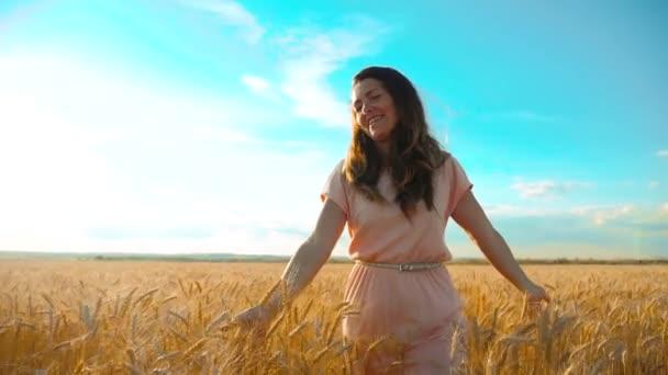 dívka je chůze po pšeničné pole příroda zpomaleně videa. Krásná dívka v životním stylu bílé šaty běh přírody svoboda štěstí ruce do strany na hřišti na světlo slunce a modrá obloha