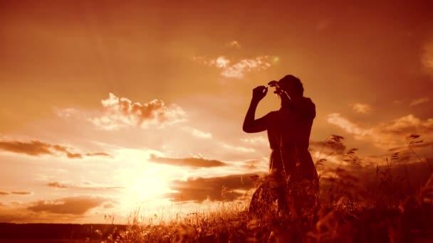 Mädchen faltete ihre Hände im Gebet Silhouette bei Sonnenuntergang. Frau, die auf Knien betet. Zeitlupenvideo. Mädchen faltete ihre Hände im Gebet zu Gott. das betende Mädchen bittet um Vergebung für die Sünden