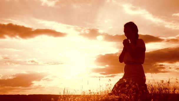 Mädchen faltete ihre Hände im Gebet Silhouette bei Sonnenuntergang. Frau, die auf Knien betet. Zeitlupenvideo. Konzept Christentum Religion Katholizismus. Mädchen faltete ihre Hände im Gebet und betete zu Gott. das Mädchen