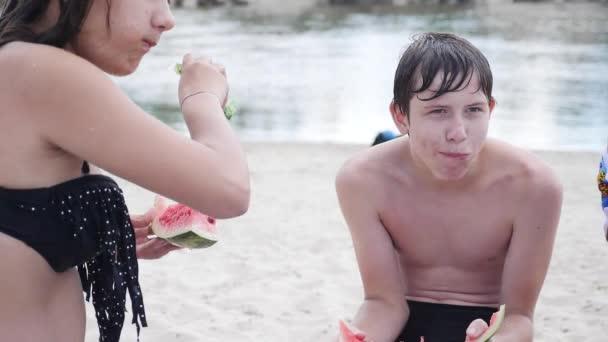 děti děti teenagery na pláži, odpočinek, smáli se a jíst meloun zpomalené video. chlapec a dívka, spočívající na pláže životní styl v létě. Teen společnost koncept