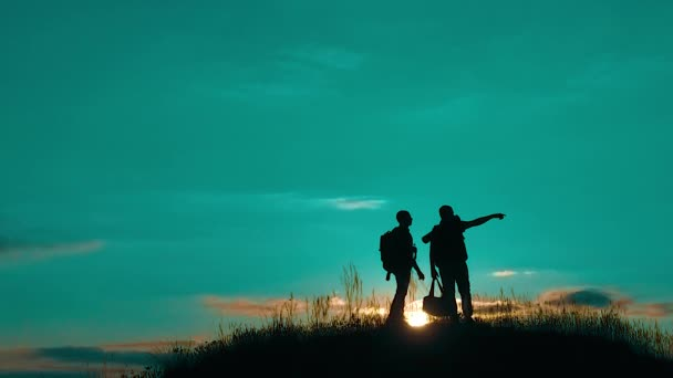 two men tourists night hikers silhouette go to the mountains sunset travel slow motion video. Traveler successful young men walking on top of Mountain and waiting for sunrise. man travel tourists in