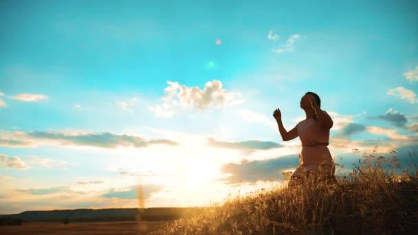 Dívka složila si ruce v modlitbě silueta při západu slunce. Žena se modlí na kolenou. zpomalené video. životní styl dívka složila si ruce v modlitbě modlit se k Bohu. dívka se modlí požádá o odpuštění za hříchy