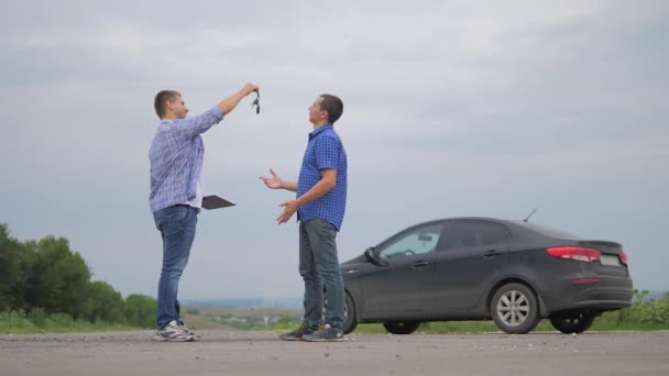 two men make a deal. man handshake hands over the keys seller driver makes car the auto insurance slow motion video sale sells used cars. Buying rent a car . man car insurance sale of lifestyle used