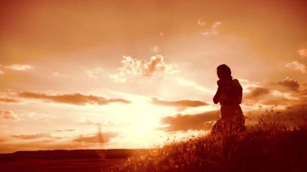 Mädchen faltete ihre Hände im Gebet Silhouette bei Sonnenuntergang. Frau, die auf Knien betet. Zeitlupenvideo. Mädchen faltete ihre Hände im Gebet und betete zu Gott. das betende Mädchen bittet um Vergebung für die Sünden