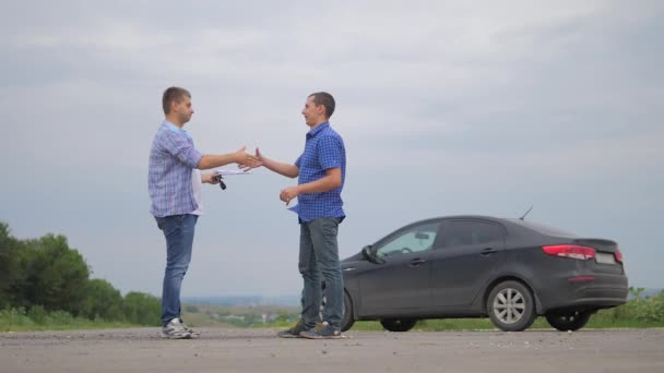 two men make a deal. man handshake seller driver makes car the auto insurance slow motion video sale sells used cars. Buying rent a car . man car insurance sale of lifestyle used cars concept