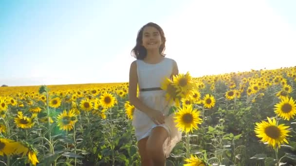 Happy little girl running happy free across the field with sunflowers. slow motion video. smelling big sunflower on summer field. Delight of a pleasant smell. Summer holiday. concept lifestyle