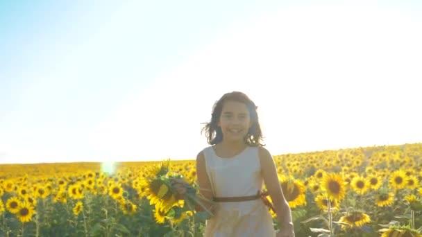 Malé radostné holčičky běží šťastný zdarma přes pole s slunečnice. zpomalené video. vonící velké slunečnice na letní pole. Radosti života příjemnou vůni. Letní dovolená. koncepce