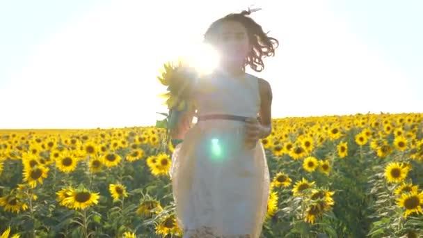 Boldog lány boldog szabadon szalad a mezőn, a napraforgó. Slow motion videót. illatos nagy napraforgó nyári mező. Örömére az életmód egy kellemes illata. Nyári szünet. koncepció
