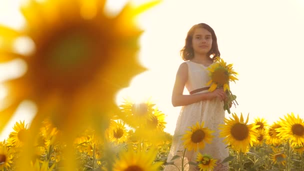 Happy little girl teen smelling a sunflower on the field in summer. slow motion video. girl teenager standing in a field with sunflowers holding flowers at sunset sunlight lifestyle. girl childhood