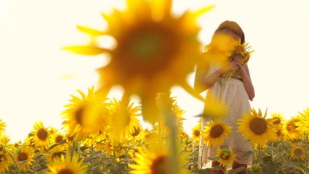 Šťastná malá holka teen vonící slunečnice na hřišti v létě. zpomalené video. dospívající dívka stojící v poli s slunečnice drží životní styl květiny na západ slunce. dívka dětství