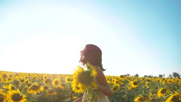 Malé radostné holčičky běží šťastný zdarma přes pole s slunečnice. zpomalené video. vonící velké slunečnice v létě životní styl pole. Radost z příjemné vůně. Letní dovolená. pojem štěstí