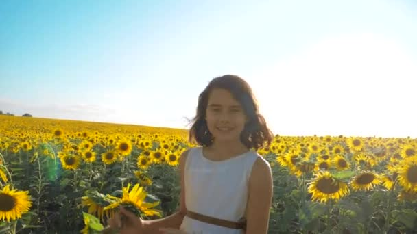 Happy little girl running happy free across the field with sunflowers. slow motion video. smelling big sunflower on summer field. Delight of a pleasant smell. Summer holiday. concept happiness