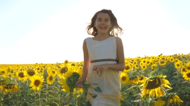 Happy little girl running happy free across the field with sunflowers. slow motion video. smelling big sunflower on summer field. Delight of a pleasant lifestyle smell. Summer holiday. concept