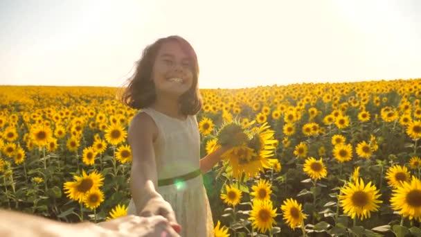 Táta a dcera chůze po poli s slunečnice při západu slunce, drželi se za ruce First-person pohled. Zpomalené video životní styl. Sleduj mě. dívku a chlapce puberťačka přejet rukou pole