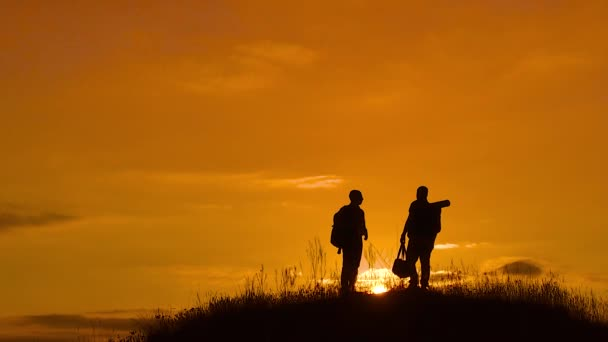 two men tourists hikers silhouette go to the mountains sunset travel slow motion video. Traveler successful young men walking on top of Mountain and waiting for sunrise. lifestyle man travel tourists