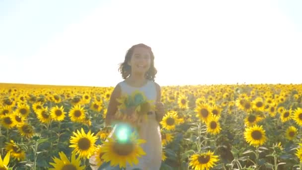 Happy little girl running happy free across the field with sunflowers. slow motion video. smelling big sunflower on summer field. Delight of a lifestyle pleasant smell. Summer holiday. concept