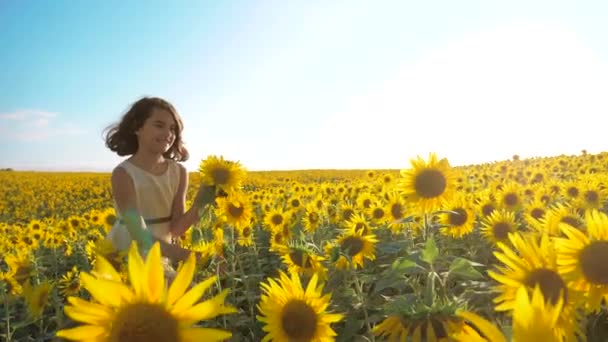 Boldog lány boldog szabadon szalad a mezőn, a napraforgó. Slow motion videót. illatos életmód nagy napraforgó nyári mező. Örömére egy kellemes illata. Nyári szünet. koncepció