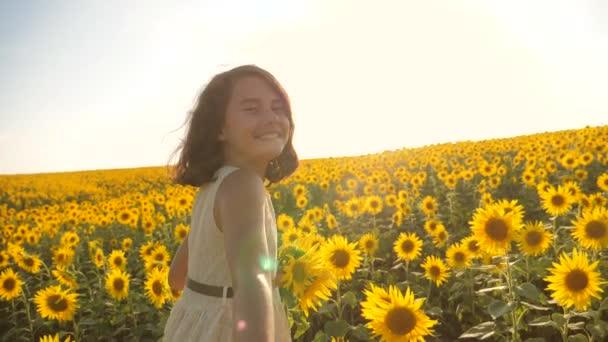 Táta a dcera chůze po poli s slunečnice při západu slunce, drželi se za ruce First-person pohled. Zpomalené video. za mnou životního stylu. dívku a chlapce puberťačka přejet rukou pole