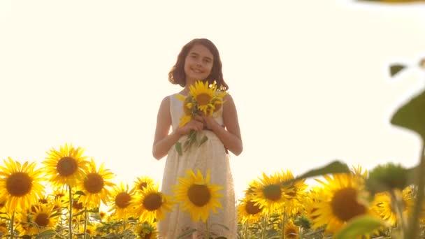 Šťastná malá holka teen vonící slunečnice na hřišti v létě. zpomalené video. dospívající dívka stojící v poli s slunečnice, držící květiny v západu slunce. dívka životního stylu dětství