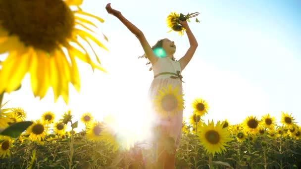 Šťastná holčička na pole slunečnic slunečního záření v létě. životní styl krásný západ slunce holčička v slunečnice. zpomalené video. Dívka teenager a slunečnice pole koncepce zemědělství