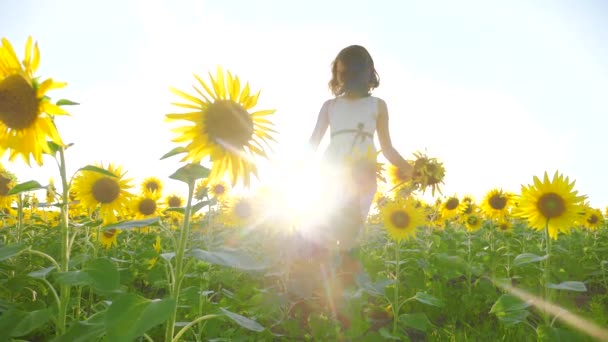 Cute child girl in yellow garden of sunflowers sunlight in summer. beautiful sunset little girl in sunflowers. slow motion video. girl teenager and sunflowers field concept agriculture lifestyle