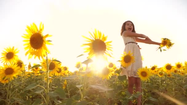 Cute child girl in yellow garden of sunflowers sunlight lifestyle in summer. beautiful sunset little girl in sunflowers. slow motion video. girl teenager and sunflowers field concept agriculture