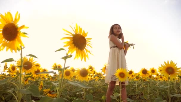 lifestyle Cute child girl in yellow garden of sunflowers sunlight in summer. beautiful sunset little girl in sunflowers. slow motion video. girl teenager and sunflowers field concept agriculture