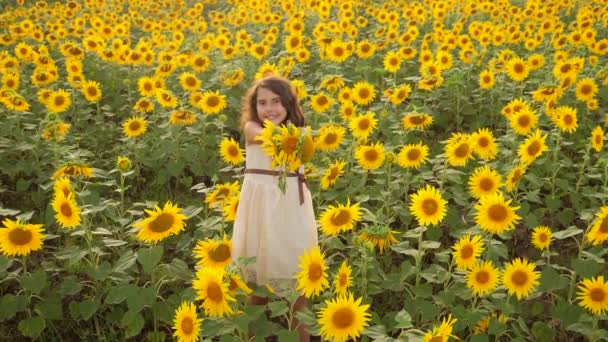 Happy little girl lifestyle on the field of sunflowers in summer. beautiful little girl in sunflowers. slow motion video. girl teenager and sunflowers field concept agriculture