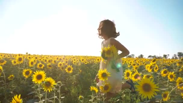 Happy little girl running happy free across the field with lifestyle sunflowers. slow motion video . smelling big sunflower on summer field. Delight of a pleasant smell. Summer holiday. concept