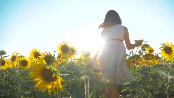 Happy little girl runs happy free across the field with sunflowers. slow motion video. smelling big sunflower on summer field. Delight of a pleasant smell. Summer holiday. concept happiness childhood