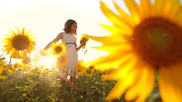 Happy little girl on the field of sunflowers sunlight in summer. beautiful sunset little girl in sunflowers. slow motion video. girl teenager and lifestyle sunflowers field concept agriculture
