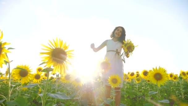 Šťastné životní styl holčička na pole slunečnic slunečního záření v létě. krásný západ slunce malá holčička v slunečnice. zpomalené video. Dívka teenager a slunečnice pole koncepce zemědělství