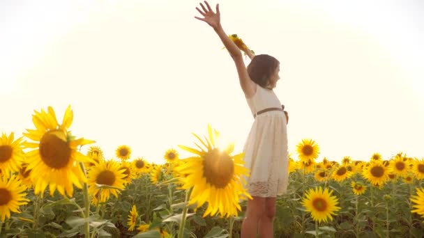 Happy little girl on the field of sunflowers in summer. beautiful little girl in sunflowers. slow motion video. girl teenager and sunflowers field lifestyle concept agriculture