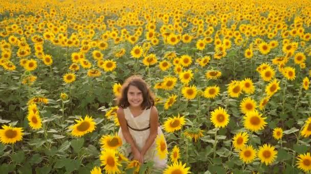 Šťastná holčička životní styl na pole slunečnic v létě. krásná holčička v slunečnice. zpomalené video. Dívka teenager a slunečnice pole koncepce zemědělství