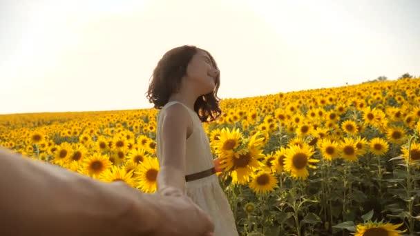 Apa és lánya, séta a területen napraforgó, napnyugtakor kézenfogva első-személy nézet. Slow motion videót. kövess. kis lány és életmód fiú tinédzser keze elgázolta a mezőt